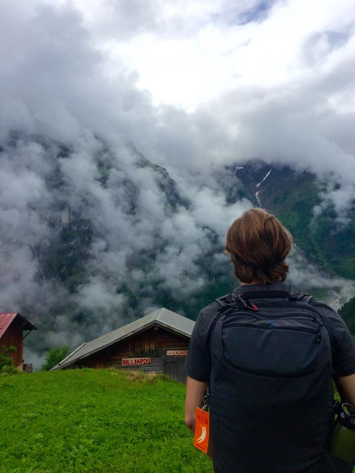 Spencer Dalby hiking up to his hostel in Gimmelwald, Switzerland with his Minaal Carry-on hiking backpack.